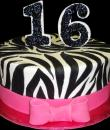 Zebra Striped 16th Birthday Cake,  White buttercream iced, round decorated with fondant zebra stripes and a pink bow.  Everything on this cake is EDIBLE.  (Serves 8-80 party slices)