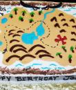 Treasure Map Birthday Cake. White buttercream iced sheet caked decorated with a treasure map, treasure chests, pirates, swords. Everything on this cake is edible. (Serves 24-98 party slices.)