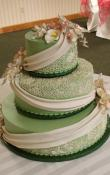 Olive Green buttercream iced,  3 tier round wedding cake decorated with Candlelight drapes and piped alencon lace . Gumpaste as the topper.  (This cake can serve receptions with 90-220 expected guests)