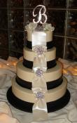 Candlelight buttercream iced wedding cake, with wide fondant ribbons and pearlescent bow loops cascading from the top tier to the bottom. Brooches are used as an accent instead of flowers but are mixed together with the monogram topper.